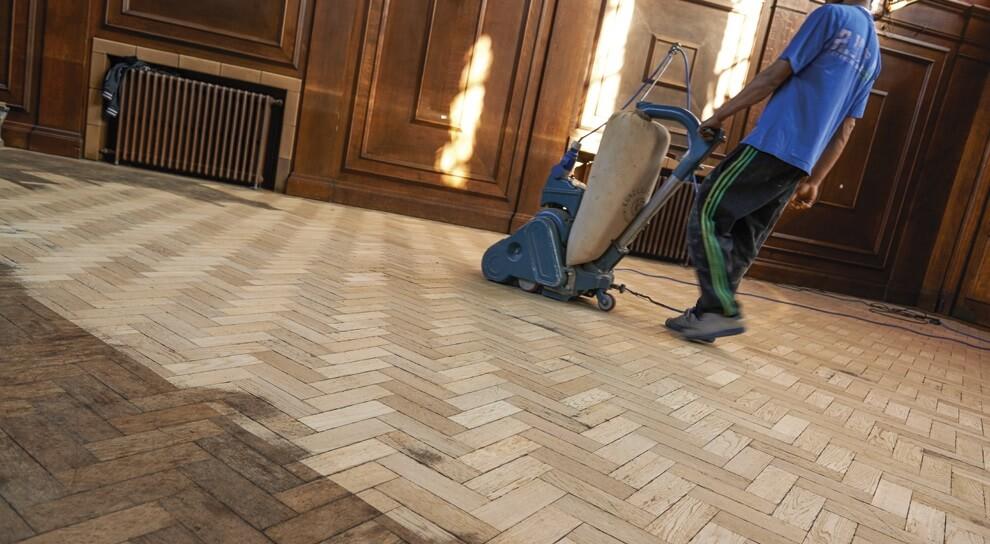 man sanding wooden floor - How To Sand A Wooden Floor: DIY Guide